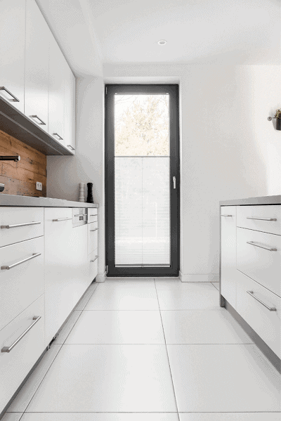narrow galley kitchen with white cabinets