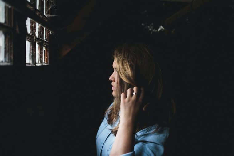 woman touching her hair while looking at the window inside house
